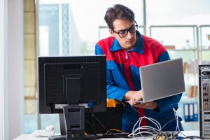 Computer repairman working on repairing computer in IT workshop